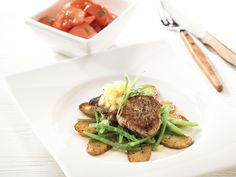 Medallions of pork with apple sauce, beans, baked potatoes and tomato salad