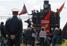 """People meet the """"Victory train"""", a vintage locomotive with members of a historical military club wearing Soviet army uniforms aboard, during the Victory Day celebration at Varshavsky railway station in St.Petersburg, Russia. (Dmitry Lovetsky/Associated Press) #"""