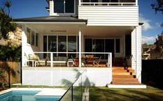 Scyon Axon Cladding adds style to a beach house veranda. The two storey home's exterior has the deep horizontal shadow lines of thick Scyon Linea weatherboards. So when it comes to the veranda the vertical grooves of Scyon Axon make a nice contrast. Adding to the contrast is a black wall behind the barbeque making it a stylish feature in this predominantly white oudoor room. The monochromatic tones are broken up with splashes of yellow. A lovely place to enjoy the morning sun.