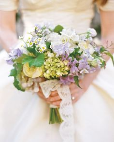 Spring bridal bouquet of freesia, lisianthus, patience roses, scabiosa, sweet peas, chamomile, garden snow roses, scented geraniums and jasmine.