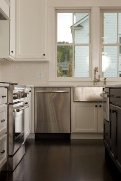 Gourmet kitchen features a black center island fitted with a microwave drawer topped with white marble.