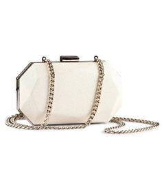 Hard-sided clutch bag with metal clasp and metal chain shoulder strap.