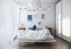 Spashes of color and unique lighting add personality to this all-white Scandinavian-style bedroom of minimal design.
