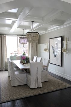 Dining Room with a pair of Light Iron/Ivory Beaded Chandeliers hung from a Coffered Ceiling over a Light Wood Trestle Dining Table, lined with Slipcovered White Dining Chairs with Tie Backs and Dark Hardwood Floors, layered with a Diamond Sisal Rug.