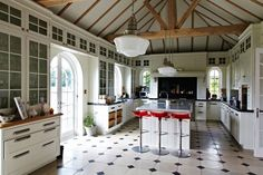 Not only do we love the glass fronted, ceiling height glass cabinets that line this vast kitchen space, but the combination of bold natural features like the wooden beams, traditional style and modern touches such as the perspex bar stools is pretty awesome too.