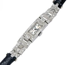 Art Deco Diamond and Platinum Wristwatch, circa 1920  The rectangular case and adjoining links decorated with round diamonds, silvered dial with Arabic numerals, joined to a black leather strap