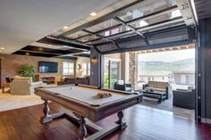 This spacious basement renovation features a garage door that links together indoor and outdoor spaces, allowing for easy transition between the pool table area and covered patio. The adjacent great room provides additional space for relaxing and entertaining.