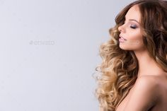 Beautiful model with long curly hair , fashion and makeup.