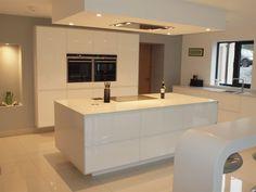 ATLANTIS KITCHENS PROJECT: Handleless Gloss White Kitchen - 12mm Silestone worktops - Siemens appliances - Quooker boiling water tap - Bespoke curved corian breakfast bar