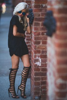 .statement hair and statement gladiator boots balanced by a simple black basic outfit.