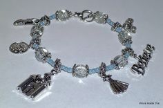 """This magical charm bracelet is inspired by the classic tale of Cinderella.   The bracelet features glass slipper, clock face, castle, dress, """"Believe"""" and pumpkin carriage Tibetan silver charms.  Made with light blue seed beads and clear crackle glass beads, Tibetan silver spacers and finished with a toggle clasp. This bracelet will add a little bit of magic to everyday."""