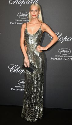 POPPY DELEVINGNE in a shimmering Roberto Cavalli gown with side cutouts and gold sequins, plus a black clutch and dangling Chopard emerald earrings, at the Chopard party.