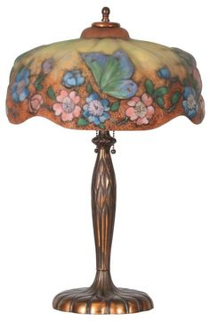 Pairpoint Puffy Table Lamp: shade is reverse painted in pastel colors with an orange and yellow background dotted with black enamel, band of alternating pink and blue apple blossoms, and 4 large colorful butterflies above.