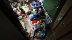 Philippines Typhoon Hagupit makes landfall.  Filipino residents rest inside a school classroom turned into a temporary evacuation center in Tacloban city