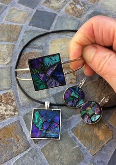 This handmade, one-of-a-kind mosaic jewelry set, features a necklace pendant, matching bracelet, and earrings. I used hand-cut purple, blue, and green van gogh glass tiles. Black grout was used to bring out the colors and grout sealant was applied to protect these pieces of wearable