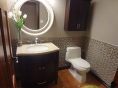 This cozy 2 pc was updated with glass and stone wall, 1 pc Kohler toilet, granite top vanity with curved solid wood doors, Bathrooms