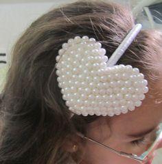 Tiara forrada de fita de cetim com um coração de contas de pérolas brancas.