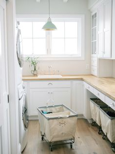 Traditional Laundry Room with Exposed beam, Hardwood floors, Pendant light, Ikea Karlby Birch Countertop, High ceiling