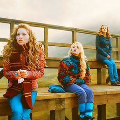 Lavender Brown, Luna Lovegood, and Hermione Granger watching the Gryffindor Quidditch Team.