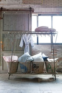 Shelf with baskets and hanging space above is great for a laundry area
