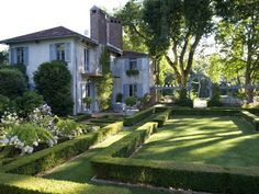 I love the formality the hedges bring to this yard... and the arched entrance    The Enchanted Home