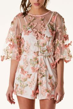 Crew neck 3/4 length sleeve romper with beautiful embroidery and patches throughout. Nude lining underneath with sheer mesh overlay. Keyhole cut out in back with button closure.