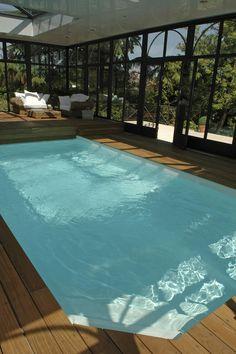 Une piscine semi enterr e avec un coin d tente au fond et for Construction piscine couverte