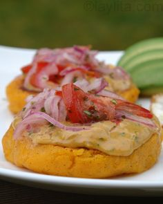 Llapingachos: Mashed potato cakes stuffed with cheese and cooked on the griddle. Topped with peanut sauce and tomato/onion curtido salsa.