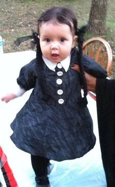 modify an existing dress (as plain as possible) by dying or painting it black, adding white buttons, collar, and cuffs. Add black tights and shoes, and braids, if necessary.