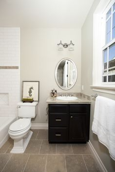 Tiny Black Bathroom Vanities with Tops and White Planted Sink under Silver Framed Oval Wall Mirror