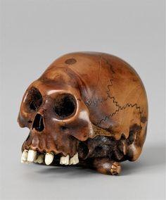 A naturalistic Edo school boxwood netsuke of a skull, by Tomochika.