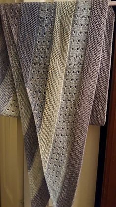 This top-down shawl uses lace or fingering weight yarn in five different colors. Hold two strands of yarn together and knit thick garter stitch stripes in this top-down triangular shawl. Short rows are added to one half of the triangle in an eyelet stitch pattern, forming a long asymmetrical shape.