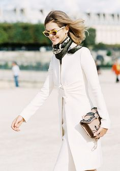 A white coat is paired with a skirt, embellished bag, and silk scarf