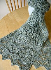 Kernel is a rectangular lace scarf knit in fingering weight yarn. Techniques include beading using a crochet hook and garter stitch grafting. The design is symmetrical: the scarf is worked from one edging through a long central panel; then, a second edging is knit and the two pieces are grafted together. The grafting is worked within a beaded garter stitch band.