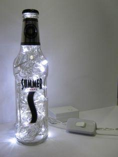 Luminária produzida com garrafa de vidro da marca Summer.  Além de original, a luminária é duplamente sustentável: a garrafa é um material reciclado e o LED consome menos energia e tem vida útil bem mais longa do que as lâmpadas comuns.  Ideal para cabeceiras, estantes e escrivaninhas. Combina também com ambientes comerciais como lojas, bares e restaurantes.  Características: - São 50 microlâmpadas brancas de LED que permitem uma boa iluminação. - Possui 8 funções. - Acompanha interruptor e…