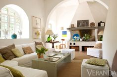 The mix of rustic furniture and contemporary art gives the living room its relaxed refinement. Pillow fabrics, Quadrille. 19th-c. Italian table. 18th-c. Italian vase. Art, Paolo Dal Pra (horse), and Leora Armstrong (blue and yellow abstract).    - Veranda.com