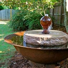 Pink granite millstone with finial and syrup kettle base make great fountain.