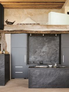 A sleek modern black kitchen with slabs of basalt used for the backsplash and the island