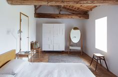 A white Alba armoire by Pinch stands next to the brand's Iona cheval mirror in a second-floor bedroom. The Moroccan rug was found in Paris; the Malm bed from IKEA was a budget buy.