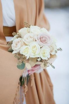 A winter bride wore a tan wrap to keep warm - her blush bridal bouquet with white roses matched perfectly. | Shelly's Designs Florist in Walker, MI
