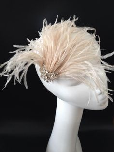 Light Pinky/Taupe Feather Bridal Hair Fascinator with a beautiful crystal button embellishment.You will feel like royalty when you slip on this stunning Chou Chou Bridal Creation! Beautiful and feminine, the Sheila piece features an array of soft and luxurious ostrich feathers finished with a crystal center adornment.  This bridal wedding fascinator is appx 5 inches tall and 6 inches long.  You can wear it with an up-do or long and flowing hairstyle, whichever pleases your style. We try ...