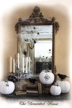 Halloween decorated entry foyer table. Black & white Halloween decor. Foam pumpkins have been painted white. One has a monogram added. The lovely old mirror has a spider web with spiders dancing from up high to down to the pumpkins and raven/crows. Antique books and silver accent the old.