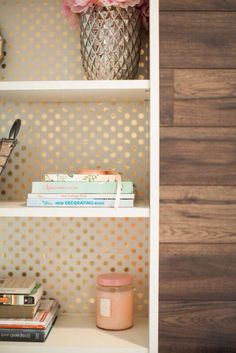 Metallic wallpaper behind bookshelf