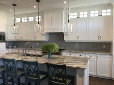 Gorgeous white shaker kitchen with Fantasy Brown granite, farmhouse sink and grey subway tile backsplash.