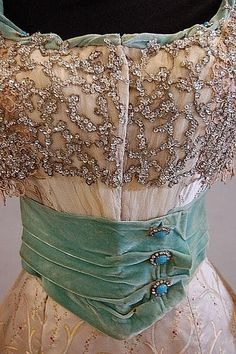 A turquoise velvet and brocaded satin evening gown, circa 1900, with elaborately sequinned and beaded bodice, the waist and cuffs trimmed with turquoise and paste studs, lace sleeves, full skirt.