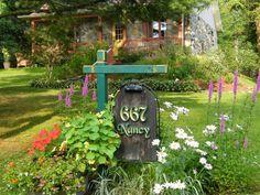 Aménagement façade - Des fleurs, le bois de grange de l'affiche, la pierre de la maison, sont les traits d'une maison de campagne ?