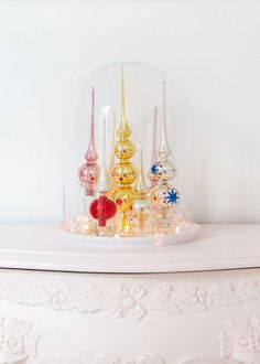 Vintage tree toppers become modern holiday bling when grouped under a glass cloche with LED lights.