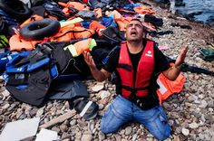 A man prays as migrants arrive on an inflatable dinghy on the Greek island of Lesbos, after crossing the Aegean sea from TurkeyA man prays as mig...