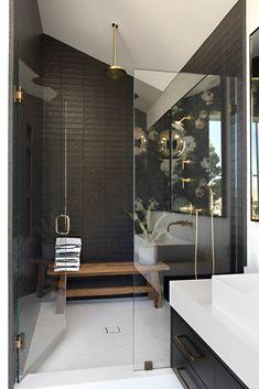 Salle de bain moderne qui allie le noir, le blanc et le doré avec un banc en bois