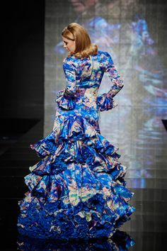 Bata de cola de satén en tonos azulina. Esta Bata de cola es de manto y es muy cómoda para bailar flamenco por su corte y por la ligereza de su vestido.